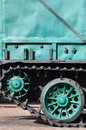 Side view of the vehicle on a caterpillar track with black tracks and green wheels and a side metal wal Royalty Free Stock Photo
