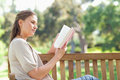 Side view of woman reading while sitting on a park bench Stock Photos
