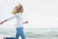 Side view of a woman running at beach smiling casual young the Stock Photography