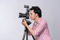 Side view of young asian photographer holding digital camera, wh Royalty Free Stock Photo