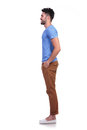 Side view of a young casual man standing in line on white background Stock Photo