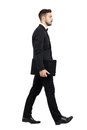 Side view of young executive carrying laptop walking full body length portrait isolated over white studio background Royalty Free Stock Photo