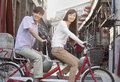 Side view of young heterosexual couple on a tandem bicycle in beijing looking at camera Stock Image