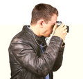 Side view from a young man with a leather jacket holding a vintage camera making a photo - Isolated. Royalty Free Stock Photo