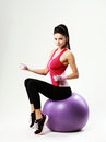 Side view of a young sport woman sitting on fitball with dumbells gray background Stock Photography