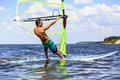 Side view of young windsurfer a passing by Stock Photos