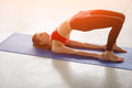 Side view of young woman doing half bridge pose Royalty Free Stock Photo