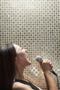 Side view of young woman singing into a microphone at karaoke shiny background women Royalty Free Stock Photography