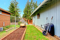 Side yard view with a small garden bed and garden carts Stock Photo