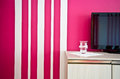Sideboard with TV and red striped wall Royalty Free Stock Photo