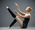 Sideview of dancing on the floor ballerina with her leg up isolated grey concept elegant art and sportive hobby Stock Image