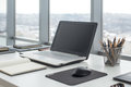 Sideview of office desktop with blank laptop and various tools. Royalty Free Stock Photo