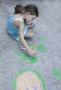 Sidewalk art a little girl uses paint and chalk to create on the Royalty Free Stock Photography