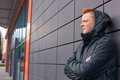 A sideways portrait of fashionable guy with trendy red hair wearing black jacket and hood on his head standing crossed hands again Royalty Free Stock Photo