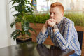 A sideways portrait of redhead guy wearing checked shirt and watch sitting in cafe at wooden table near green palm tree holding hi Royalty Free Stock Photo