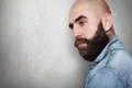 A sideways portraitwith copy space of fashionable bald hipster having tattoo on his neck, thick black eyebrows and beard, big dark Royalty Free Stock Photo