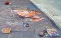Siena, Italy - August 18, 2013: Street artist painting on asphalt chalk portrait of a girl. . Street art.
