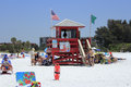 Siesta beach lifeguard station key florida may red tower flying green and american flags with a present and lots of people around Stock Images