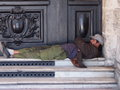 Siesta time man taking a on marble steps in front of a black door Royalty Free Stock Photography