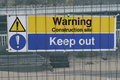 A sign on a building area with the text Warning construction site keep out Royalty Free Stock Photo