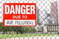 Sign danger due to air pollution hanging on the fence