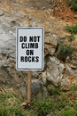 Sign do not climb on rocks planted in the grass in front of rocky ground Royalty Free Stock Image