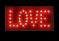 Sign of love featuring illuminated electric light bulbs that form the word against red painted wood background Royalty Free Stock Images