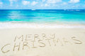 Sign marry christmas on the sandy beach by ocean holiday concept Stock Image