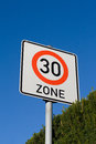 Sign maximum speed german zone of on a hedge deep blue cloudless sky Stock Image