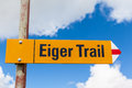 Sign post showing the eiger trail of swiss alps indicating hiking under feet of famous north face with blue sky and Stock Photo