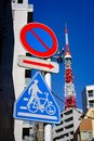 The sign prohibits the car to drive into, Direction sign and Bicycle Leash Sign with Tokyo Tower and buildings backgrounds Royalty Free Stock Photo