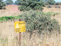 A sign reading `Danger Mines!`  hangs from  a barbed wire fence in the Golan Heights, near the border with Syria, Israel Royalty Free Stock Photo