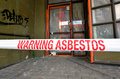 Sign reads warning asbestos removal in progress christchurch dec inhalation of fibers can cause serious and fatal Royalty Free Stock Photos