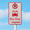The sign shows way to bus stop and no parking area with blurry b blue sky background Stock Photo