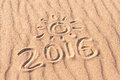 Sign 2016 and sun written on sandy beach. Summer travel concept