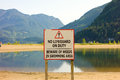 A sign warning swimmers to use the lake at their own risk Royalty Free Stock Photo