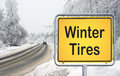 Sign for winter tires yellow warning with black text reading beside a snow and ice covered road with forest on either side Royalty Free Stock Images