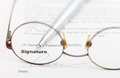 Signature of contract and pen through eyeglasses Royalty Free Stock Photo