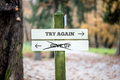 Signboard with two signs saying try again give up pointing in opposite directions the sign scribbled through Stock Photo