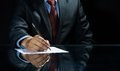 Signing a deal close up of businessman sitting at table and document Royalty Free Stock Photo