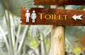 Signpost wood with toilet symbol text and arrow Royalty Free Stock Photo