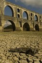 Signs of drought fractured ground dam with aqueduct behind Royalty Free Stock Photos