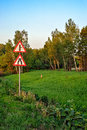 Signs on roadside and forest around in sunset light Royalty Free Stock Photos