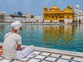 Sikh devotee at the harmandir sahib golden temple amritsar india march sitting by pool in front of while tourists and pilgrims Stock Photography