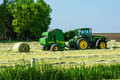 Silage baler a parked john deere and tractor on a harvested farm hay field please note i upload my images to both dreamstime and Royalty Free Stock Images