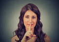 Silence gesture closeup of young woman holding placing finger on lips gray wall background Royalty Free Stock Image
