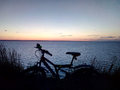 stock image of  Silhouet a bicycle against the background of grass and sunset over the river or sea