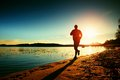 Silhouette of active man running and exercising on the beach at sunset. Royalty Free Stock Photo