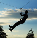 Silhouette of alpinist hang on rope against sky Stock Photo