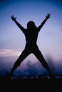 Silhouette back view of woman enjoying and jumping at riverside. Royalty Free Stock Photo